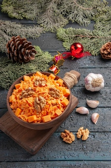 Vista frontale insalata di carote grattugiate con noci e condimenti sulla scrivania blu scuro insalata di alimenti salutari dieta color