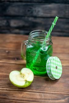 暗い果物の飲み物の写真のカクテル バーの色に新鮮なリンゴが入った缶の中の青リンゴ ジュースの正面図