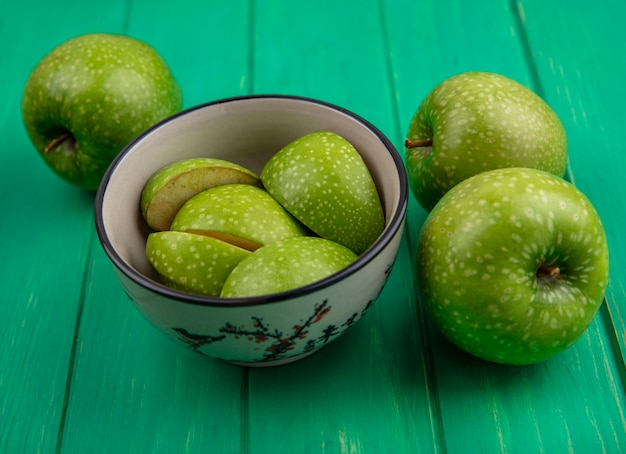緑の背景に全体とボウルの正面図青リンゴスライス