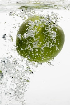 Front view of green apple in water