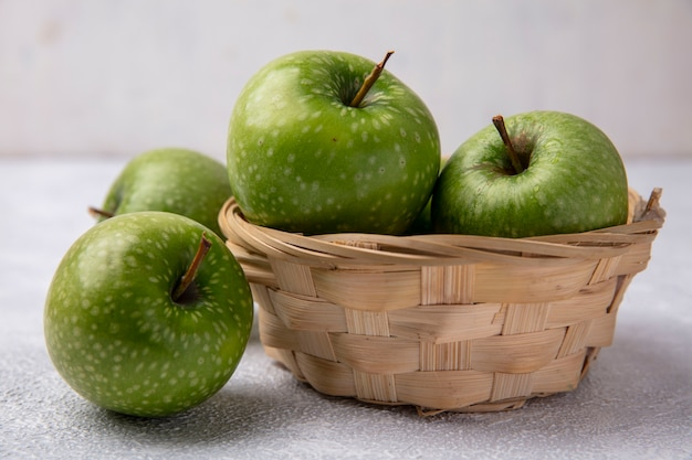 Vista frontale mele verdi in un cesto su uno sfondo bianco