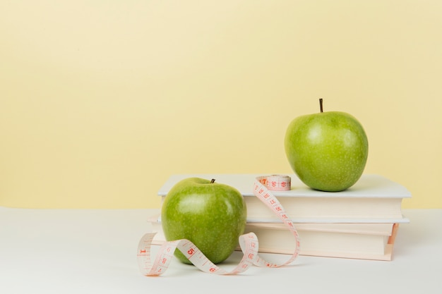 Front view of green apples on books with copy space