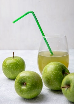 Vista frontale mele verdi con succo di mela in un bicchiere e una cannuccia verde su sfondo bianco