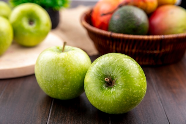 Front view of green apples with a bucket of fruits like mango pear on a wooden surface