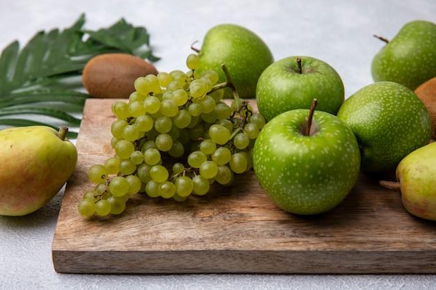 Vista frontale mele verdi con uva verde su un supporto con una pera su uno sfondo bianco