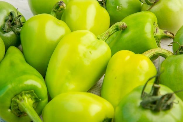 Vista frontale peperoni verdi con pomodori verdi su scrivania bianca colore insalata matura foto pasto dieta vita sana