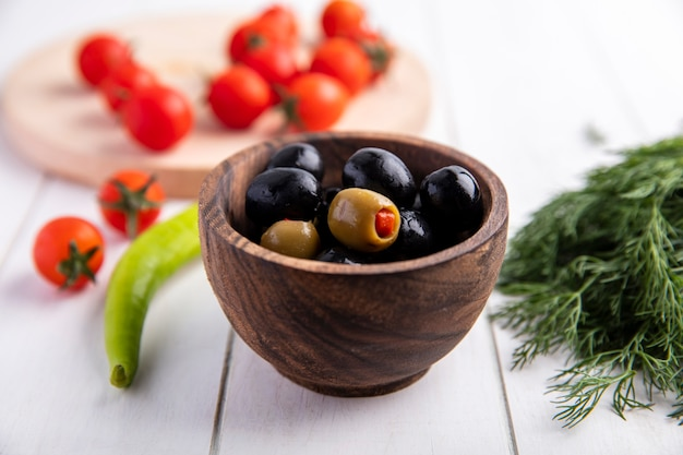 Front view of green and black olives in bowl and tomatoes pepper and dill on wooden surface