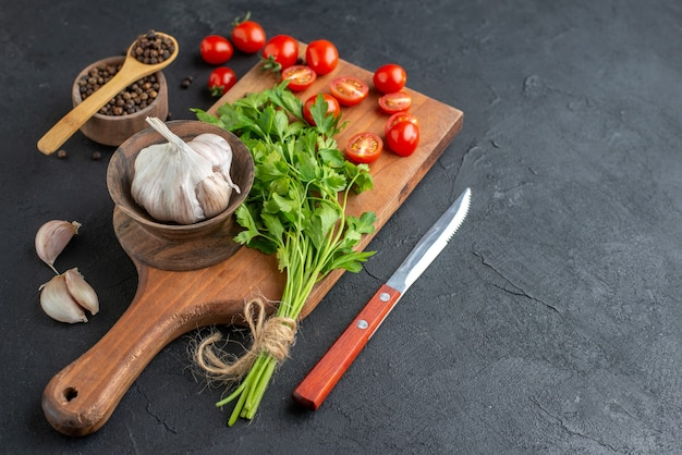 Vista frontale del fascio verde fresco intero di pomodori tagliati aglio su tagliere di legno coltello pepe su superficie nera in difficoltà