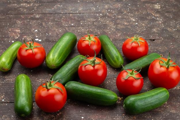 Вид спереди зеленые огурцы свежие и спелые с красными помидорами на коричневый, овощное растение дерево еда