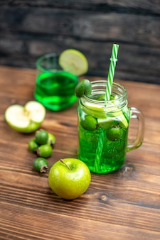 Vista frontale succo di feijoa verde all'interno lattina con mele verdi su scrivania in legno bar cocktail di bevande colorate alla frutta