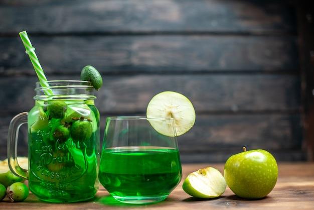 正面から見た緑のフェイジョア ジュースと新鮮なリンゴとフェイジョアをダークバーのフルーツカラー写真カクテルドリンク