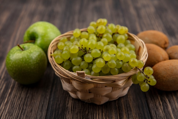 Front view green grapes in a basket with green apples and kiwi on a wooden background