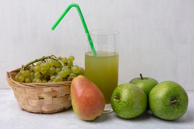 Вид спереди зеленый виноград в корзине с грушевыми зелеными яблоками и яблочным соком с зеленой соломинкой в стакане на белом фоне