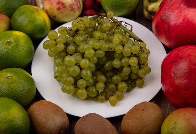 Uva verde di vista frontale su un piatto con i mandarini ed i melograni del kiwi