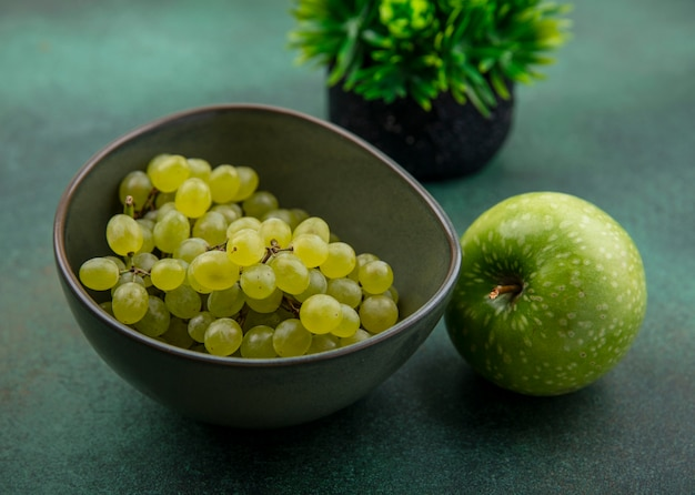 緑の背景に青リンゴと正面図緑のブドウ
