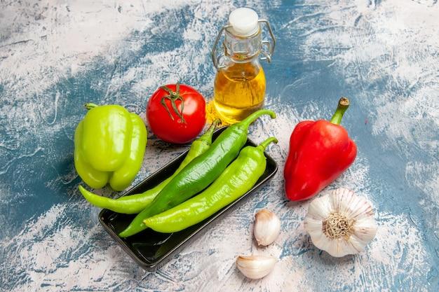 Peperoncini piccanti verdi di vista frontale sul rosso del pomodoro del piatto nero e aglio dei peperoni verdi su blu-bianco