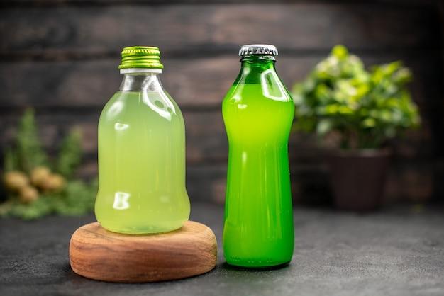 暗い木の表面の木製ボードレモネードのボトルの正面図青汁