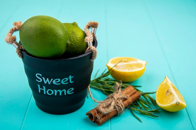 Front view of green lemons on a black bucket with yellow lemon slice and cinnamon sticks on blue surface