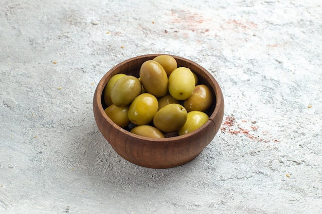 Зеленые оливки, вид спереди, внутри маленькой тарелки на белом пространстве