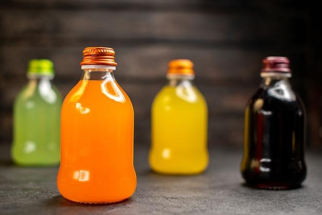 正面図緑、オレンジ、黄色、黒のフルーツジュースボトル