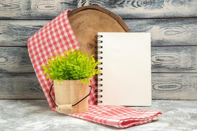 灰色の背景にメモ帳と正面図緑の植物植物の木の花の机