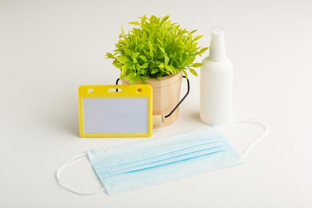흰색 표면에 스프레이와 마스크 전면보기 녹색 식물