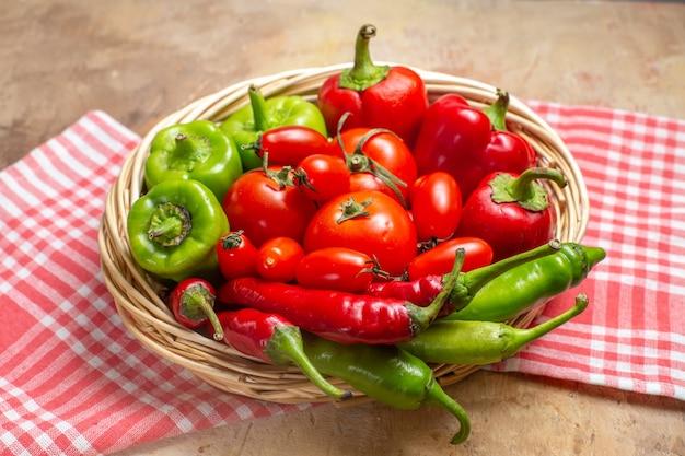 Vista frontale peperoni verdi e rossi peperoncini pomodori in cesto di vimini e asciugamano da cucina su sfondo ambrato
