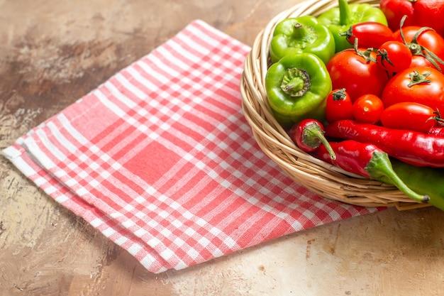 Vista frontale peperoni verdi e rossi peperoni pomodori in cesto di vimini asciugamano da cucina su ambra