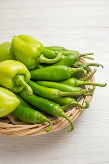 正面図緑のスパイシーな唐辛子と白い背景色のバスケット内のピーマンホットエッジの効いた野菜サラダ写真熟した