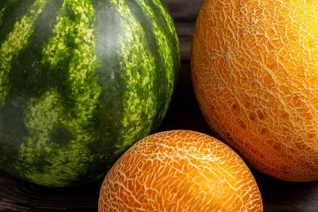 正面緑のスイカ丸い形が茶色の机の上のメロンと新鮮でジューシーなフルーツを形成