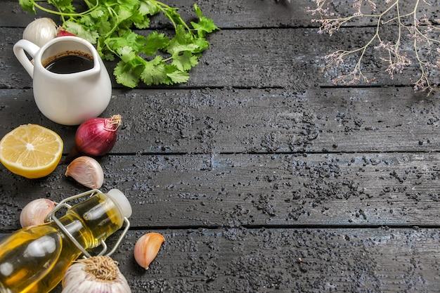 暗い机の熟した食事の色にニンニクと油と正面の緑とレモン