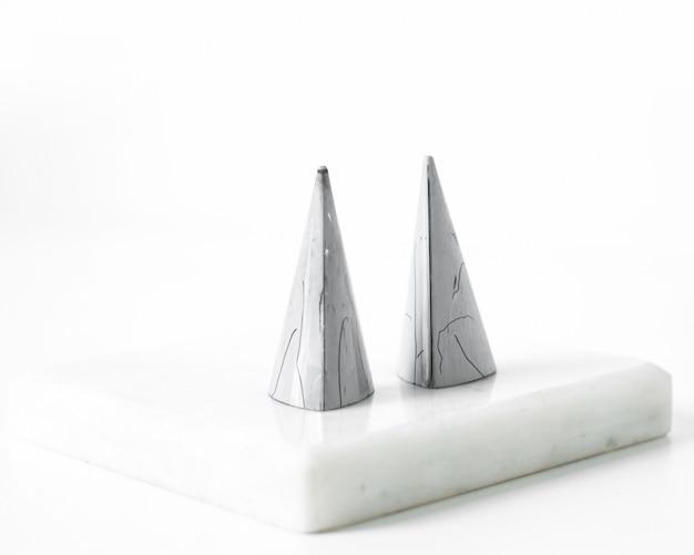 Cappucci grigi di vista frontale sulla superficie bianca