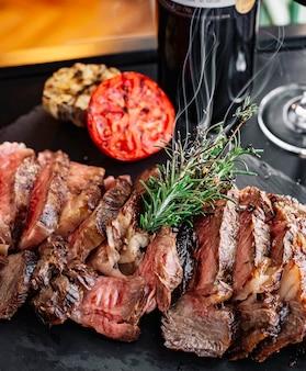 Вид спереди на гриле мясо с розмарином и ломтиком помидора на доске