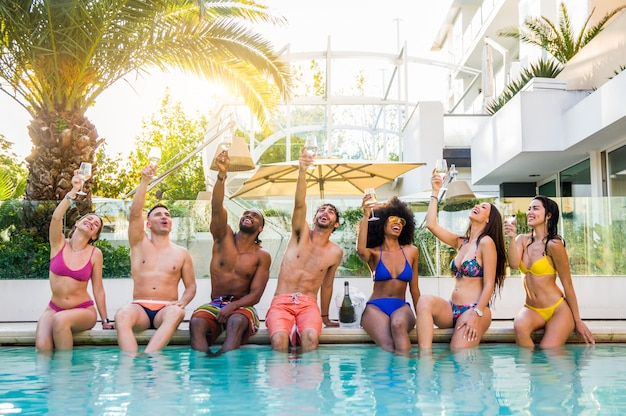 Front view of group of friends at swimming pool party celebrating with white wine champagne