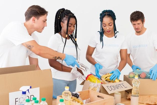 寄付の世話をするボランティアの正面グループ
