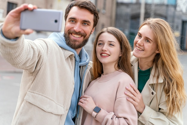Front view of group of smiley friends outdoors in the city taking selfie