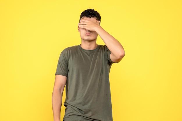 Vista frontale del ragazzo che si copre il viso con la mano