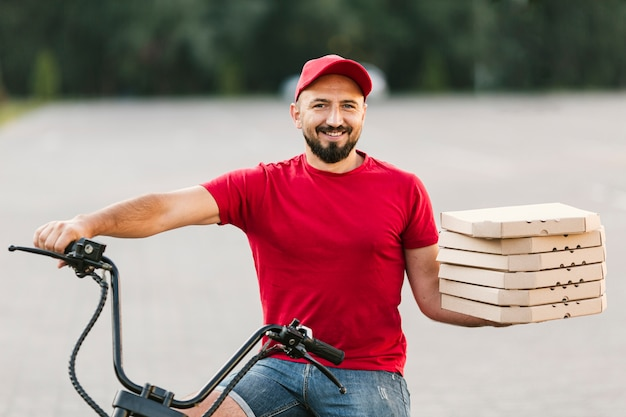 Front view guy delivering pizza order