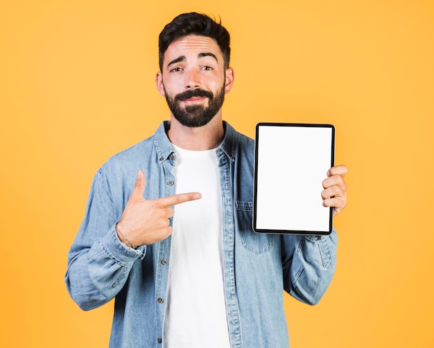 Front view guy pointing at a tablet
