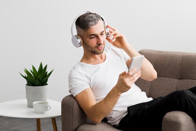 Вид спереди парень с наушниками, глядя на свой телефон