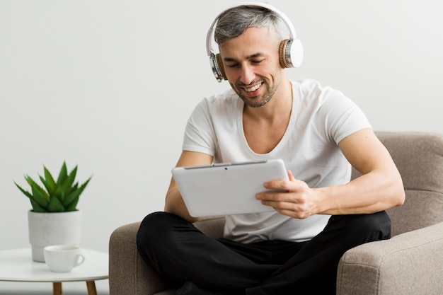 Front view guy with headphones sitting on a chair
