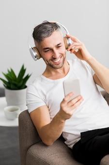 Вид спереди парень с наушниками, улыбаясь на свой телефон