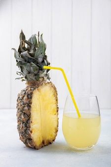 Front view of half of pineapple and glass of pineapple juice with drinking tube on white surface
