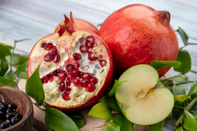 Front view of half pomegranate with a branch of leaves and an apple on a gray surface