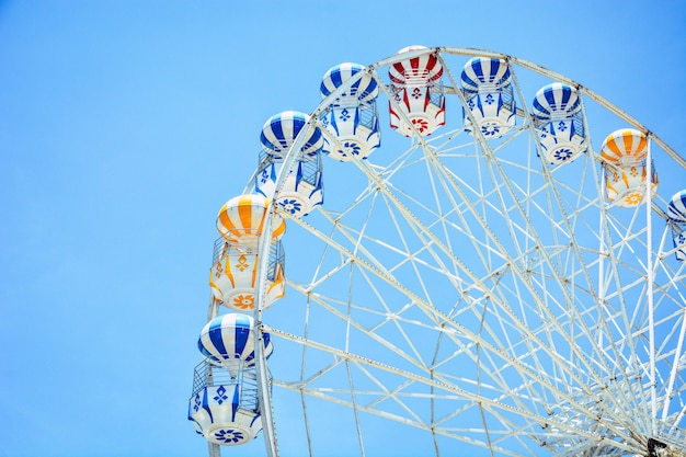 Front view of half retro colorful ferris wheel at amusement park over blue sky background