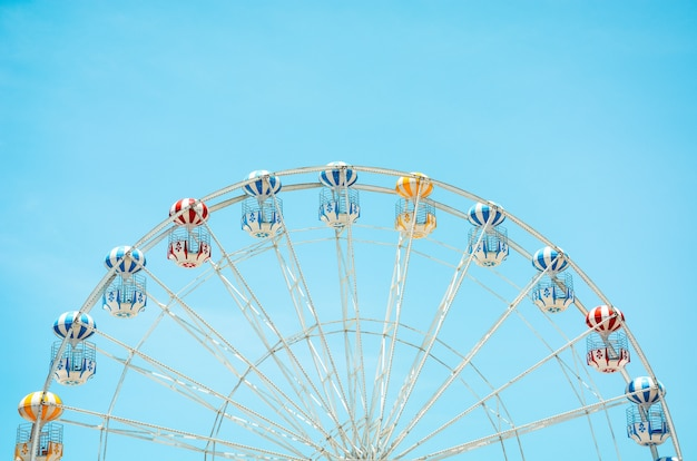 Front view of half retro colorful ferris wheel over blue sky background