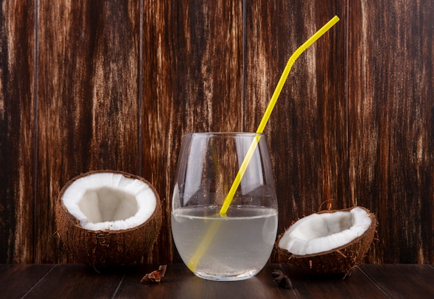 Front view of halved and fresh coconuts with a glass of water on a wooden surface