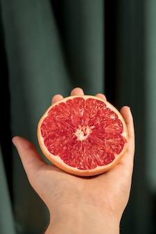 Front view halved grapefruit on hand