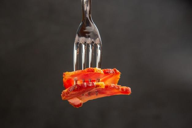 Fetta di prosciutto vista frontale su forchetta cibo foto a colori carne scura