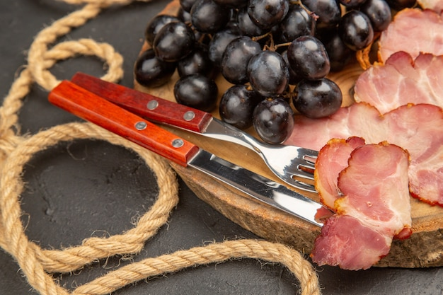 Fette di prosciutto vista frontale con focacce uva e fette di pane su foto a colori scuri snack a base di carne